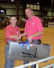 Blaine McDougal, left, is finishing a successful summer on the hog-showing circuit.  Blaine, pictured with hog show official Mark Gray, was named champion junior showman at the National Junior Swine Association's Southwest Regional. He also showed the reserved champion Yorkshire breeding gilt at the Kansas Sate Fair.