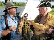 Lynette Trotter, left, and Walter Gotsch hold two of the various items the Lewis and Clark re-enactors have created. Trotter, a Lansing resident, holds a braided rope bumper similar to what may have been used to protect the boats' sides. Gotsch, of St. Louis, holds a piece of inscribed leather similar to ones the group was thought to have given as souvenirs.