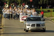 The Lansing High School marching band follows a Lansing Police car at the front of the LHS homecoming parade on Wednedsay, Sept. 20.