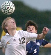 Jonas Box (left) tries to control the ball against the attack of Mill Valley's Alex Linthicum Wednesday.