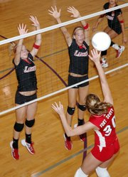 Lansing High players Sara Logan, left, and Brittney Lang go up for a block against Osawatomie.