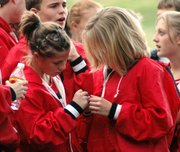 Lansing High freshmen Abbey Lozenski, left, and Lauren Jaqua inspect their medals Thursday at the Lansing Invitational. Lozenski placed eighth in the varsity girls race and Jaqua placed first.