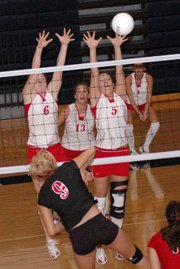 Tonganoxie's Tracie Hileman, left, and Elizabeth Baska, right, attempt to block a spike by Lansing freshman Rachel Milnark.
