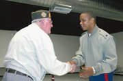 De Soto veteran Herb Wood shakes the hand of Marine Sgt. Belvin Ware. Wood was presented with two awards and a medal for service in World War II and the Korean War.