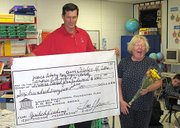Mary Noyes, Lansing Elementary School first-grade teacher, right, reacts as the Lansing Educational Foundation Fund prize patrol tells her what she's earned. LEFF advisory board president Tom Young and fellow board members delivered the news Tuesday that Noyes and five other teachers had received an Educate the Pride minigrant to help fund a reading project at LES.
