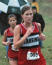 Lori Flippo, Lansing High senior, and freshman Abbey Lozenski race toward the finish line Saturday at the Class 5A regional cross country meet.