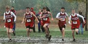 The Lansing High boys splash through the mud at the start of the regional cross country race Saturday at Shawnee Mission Park.