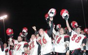 Lansing High players celebrate after advancing to the football state playoffs for the third straight year.