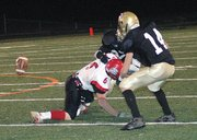 Lansing High junior defensive end Justin Smith pops the ball loose from Turner receiver M.J. Bland.