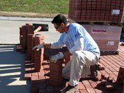Ifo Atagi, of Realm Construction, Blue Springs, Mo., positions bricks in the median under construction on Main Street north of Mary Street.