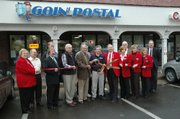 Kenny Elkins, center, is surrounded by members of the Leavenworth-Lansing Area Chamber of Commerce and Lansing dignitaries at a ribbon-cutting ceremony at Goin' Postal, a new mailing services shop in the Main Street Center. Elkins is the shop owner. The ribbon-cutting took place Tuesday, Nov. 28.