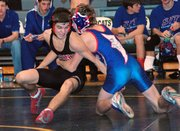 Lansing High senior Scott Keller tries to break free of his Santa Fe Trail opponent's grip at 119 pounds.