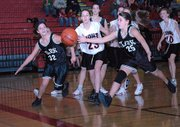 Lansing Middle School seventh-grader Gabby Hacker, middle, battles Clark players Megan Scott, left, and Bobbi Allred, right, for a ball during the first half Saturday at LMS.
