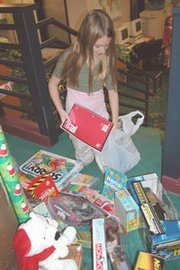 "Mize Elementary School fifth-grader Morgan Koelzer from De Soto, donates school supplies and toys to the ""Just Like Me"" toy drive this week. Students brought brand-new toys and gifts to help needy families this Christmas."