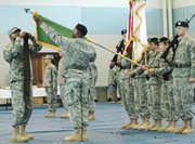 Lt. Col. Patrick Williams, left, cases the colors of the 705th Military Police Internment and Resettlement Battalion during a departure ceremony Friday, Dec. 1, at Fort Leavenworth. A unit from the battalion will deploy to a mission in Iraq.