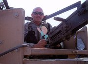 Flat Stanley receives a ride in a tank from Army Spc. Thomas Tomrell during the paper cutout's visit to Iraq.