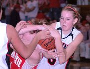 Lansing High sophomore Brittney Lang, right, gets tangled up with Tonganoxie's Tracie Hileman.
