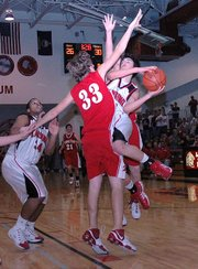 Lansing High sophomore point guard Curtis Beall is fouled while going up for a shot against Tonganoxie. Beall scored a career-high 15 points in the 54-46 loss.