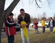 Ben Rogers, left, helps his father, Maj. Dave Rogers, remove a yellow ribbon from a tree at Lansing Elementary School. Dave Rogers returned to the United States in November after a one-year deployment to Iraq.