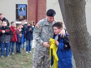 Sgt. James Fouquet hugs his son Christian Fouquet, a third-grader at Lansing Elementary School, during a ceremony at LES. The pair cut down a yellow ribbon in celebration of James Fouquet's safe return home from a peacekeeping mission in Kosovo.