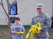 Dylan Lash, left, celebrates with his stepdad, Army Staff Sgt. Chad Pappas, during a yellow-ribbon cutting ceremony.