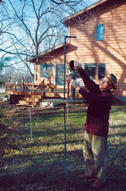 Roger Boyd fills one of the many bird feeders in his back yard in Baldwin City.