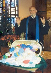 The Rev. Gerald Vaughn of the De Soto United Methodist Church blesses the 400 stocking caps women of his congregation and the De Soto Baptist Church knitted and crocheted for babies in Africa. Keeping a baby's head warm greatly increases the newborn's chances of survival.