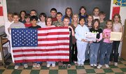 Lansing Intermediate School fourth-graders display an American flag that was flown over the U.S. Military Headquarters in Baghdad, Iraq, during Operation Iraqi Freedom. Maj. Mark Zinser, of Leavenworth, gave the flag to Barb Munsterman's class, which includes his son Chase Zinser, who is holding the flag on the far left.