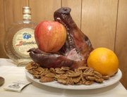 the head of the roasted pig sits on a table with the bottle of plum brandy - When Is Serbian Christmas