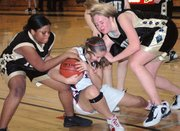 Lansing High sophomore Cassandra Murphy fights for a loose ball during the junior varsity girls basketball team's victory over Turner.