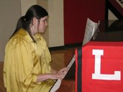 Lansing High School senior Mary Lyon provides the entertainment before the National Honor Society induction ceremony.