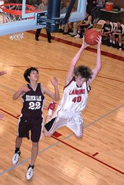 Lansing High junior Will Johnson pulls down a rebound during the first half Thursday against Silver Lake.