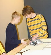 LTMS seventh-graders Philip Kaul, left, and Parker Riley carefully place a robot they helped build as members of a nine-member robotics competition team on a game table. Team coach Sarah Brown built the table with the help of LTMS seventh-grader Chris Dunn.