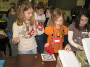 Lansing Intermediate School fourth-graders, from left, McKenzie Hersh, Kristen Tomrell and Stevie Sherard try their luck in a Dodge City dice game to earn a prize during Kansas Days.