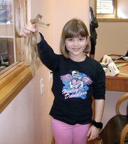 Shelby Herring, a Lansing Elementary School third-grader, shows off her second donation to Locks of Love, a nonprofit organization that provides hairpieces to financially disadvantaged children who suffer from long-term medical hair loss.