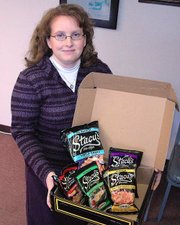 Lansing resident Stacy Cook shows off the box of Stacy's pita chip snacks that was delivered to her just days before her birthday. The package didn't include a birthday card, which perplexed Cook. But she later found out she was a recipient in a nationwide marketing blitz by Stacys in which the chips were sent to people named Stacy.
