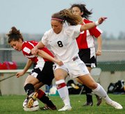 Bianca Manago, Lansing High senior, fends off a Blue Valley player during a game last year.