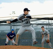 De Soto senior Tyler Farmer pitches in Tuesday's second game with a runner on base.