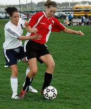 Christine Cordes, Lansing High junior, shields the ball from Mill Valley's Jennifer Volmer during Lansing's 3-2 victory Tuesday.