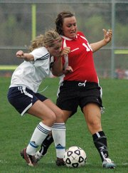 Lansing High junior Erin Griffen tangles with a Mill Valley player while battling for the ball during the first half Tuesday.