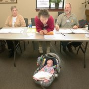 Election worker Patti Combs (center) kept a watchful eye on Kelsey O'Donnell on the floor in a car seat while her mother Lisa cast her ballot nearby Tuesday at Sacred Heart Church.