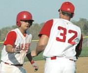Lansing High junior Johnny Stratton is congratulated by coach Troy Andrews after blasting a three-run homer in the season-opener against Immaculata.