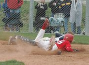 Lansing High senior Mike Nielsen dives safely past the catcher during a close play at the plate against Mill Valley.