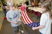 Mize Elementary School fourth-grader Nick Mullen reads instructions to Kristen Knapp and Jordan Gorkos (right) on how to fold a flag that came with a trunk from the Kansas Historical Society, which provided lessons on early Kansas history.