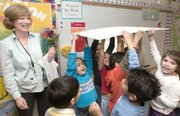 Students cheer as they lift the giant grant check that was awarded to teacher Marianne Gray (left) Thursday morning at Shawanoe Elementary School.