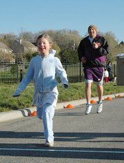 Emily Krueger, 7, sprints to the finish line of the one-mile run on Sunday morning at Towne Center. Not far behind is her father, Paul Krueger.