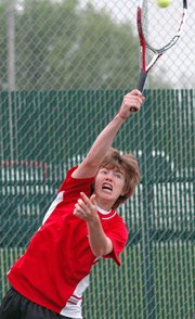 Lansing High sophomore Ezra Carpenter serves during his doubles match Thursday at the Class 5A regional tournament.