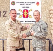 Lt. Commander Dave Buehler, left, exchanges military coins with Master Sgt. Brian Anderson. The two Lansing residents are roommates at Victory Base Camp in Baghdad, Iraq.