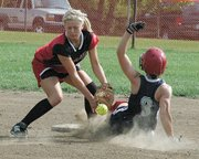 Mill Valley's Carleigh Berry steals second base as Lansing High freshman shortstop Rachel Milnark tries to tag her out.