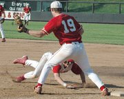 Peter Gibson, Lansing High sophomore, dives safely back to first base during the first inning against Tonganoxie.